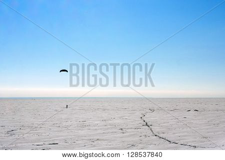Silhouette of a man kiting in winter time at frozen lake