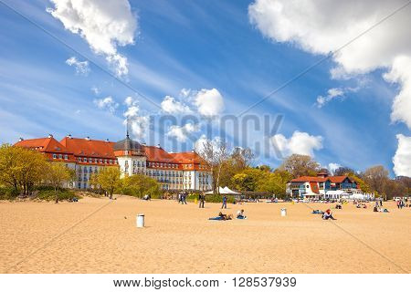 SOPOT, POLAND - MAY 03, 2016: People relaxing on beach on the second plane beautiful architecture of Sopot. Sopot is a famous tourist resort located in Poland.