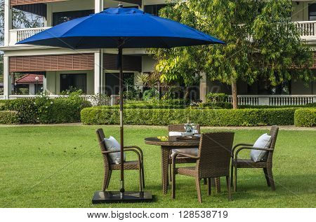 Rattan furniture table chairs umbrella and outdoor pillows