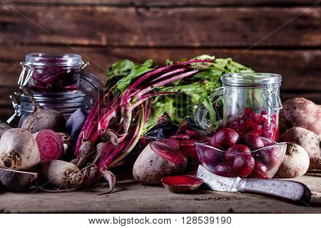 Beetroots in slices balls chips and fresh beet leaves with old knife