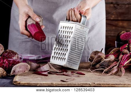 Cook in gray apron is preparing to grate a beetroot with vegetable rasper