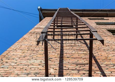 Rusty fire escape on red brick wall