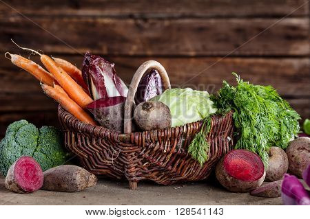 Basket full of healthy vegetables like carrots beetroot curly kale chicory broccoli cabagge