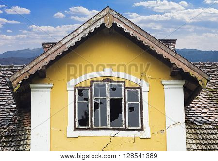 Abandoned old yellow house with vandalized windows.