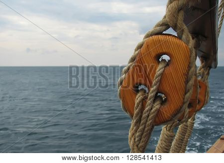 Close-up of Mast on traditional sailboats. Macro large wooden detaile of the ship. Beautiful travel picture with masts and rigging of sailing ship on the blue sky background.