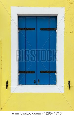 Picturesque old window with blue shutters on light yellow wall (Burano island Venice Italy)