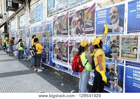 Buenos Aires Argentina - 14 January 2011: Pubblic workers detaching and cleaning city walls of posters