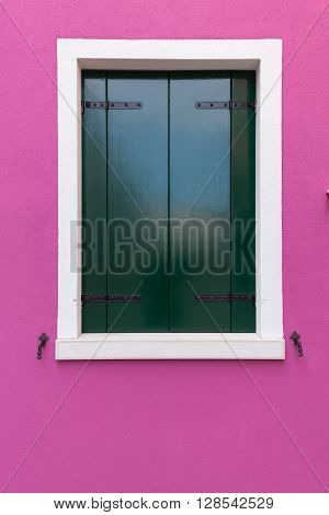 Picturesque old window with dark green shutters on pink (fucsia) wall (Burano island Venice Italy)