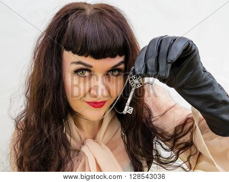 Attractive woman holding a key with gloved hand