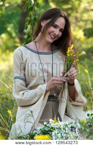 Beautiful brunette woman with field flowers