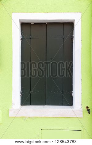 Picturesque old window with dark green shutters on light green wall (Burano island Venice Italy)