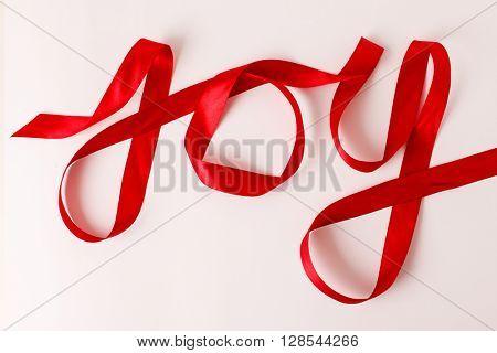 Joy word written in red ribbon on white background