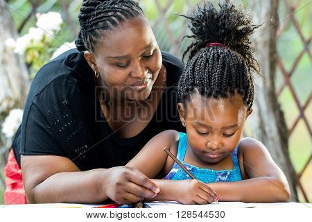 Close up portrait of african teacher supervising little kid doing homework outdoors.