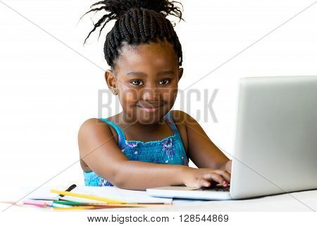 Close up portrait of little african girl sitting at desk with hands on keyboard.Isolated on white background.