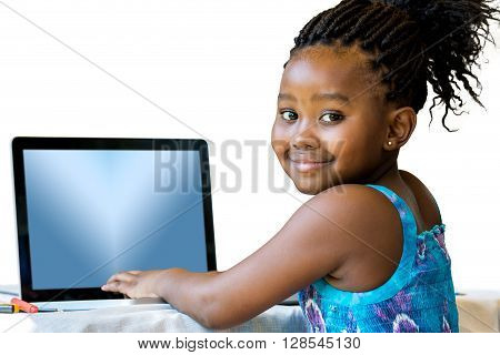 Close up portrait of little african girl typing on laptop.Isolated on white background.
