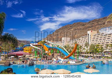TAURITO, GRAN CANARIA, SPAIN - APRIL 21, 2016: Tourists on sun holidays at the Lago Taurito aquapark in Taurito, Gran Canaria. Taurito is very popular tourist destination