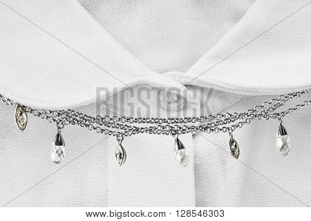 Chain necklace on white blouse closeup as a background