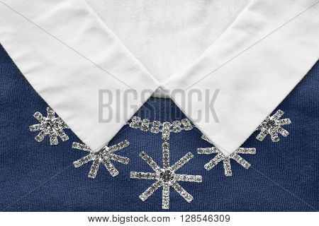 Diamond necklace on blue pullover with white collar closeup