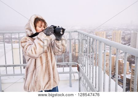 Woman in fur jacket takes pictures of city standing on building roof in winter.