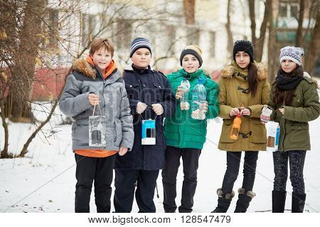 Five children stand together, holding home-made bird feeders with seeds and crumbs.