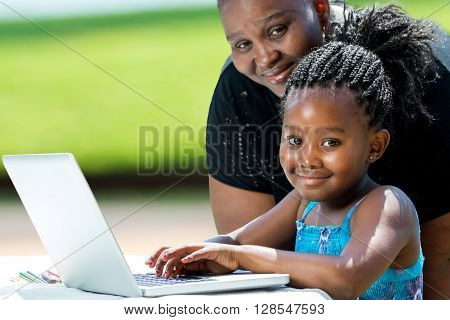 Close up portrait of little african girl with braids and mother with laptop.Kid typing on laptop against green background outdoors.