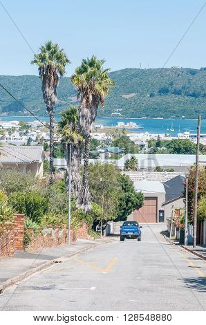 KNYSNA SOUTH AFRICA - MARCH 3 2016: A street view of Knysna with the Regional Office of the South African National Parks Board on the historic Thesens Island in the back