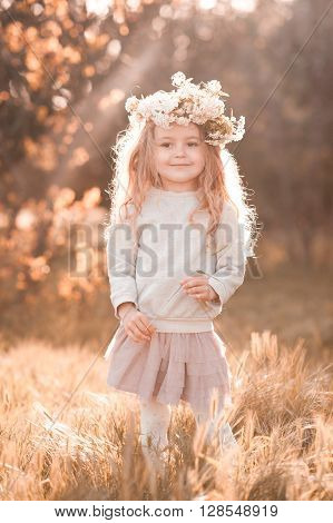 Cute baby girl 4-5 year old walking in park wearing flower wreath. Looking at camera. Childhood.