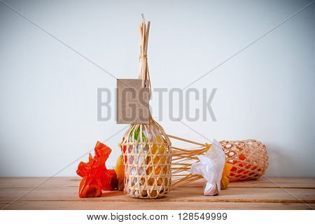 colorful thai sweets in Wicker round bamboo basket on wooden background with blank paper for note