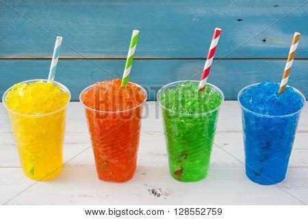 Fresh colorful summer slushies on blue wood