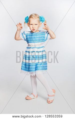 Portrait of beautiful blonde little girl. Girl grimaces