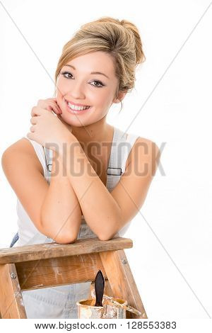 Smiling blonde girl in overalls resting on old ladder