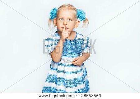 Beautiful baby girl on a white background making shh