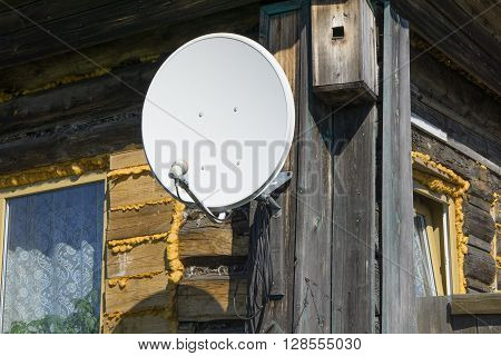 Satellite dish on a wall of wooden village house