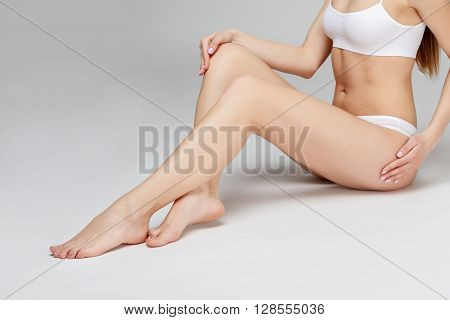 Studio shot of perfect female legs on grey background