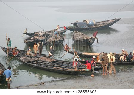 GOSABA, INDIA - JANUARY 17: wooden boat crosses the Ganges River January 17, 2009 in Canning Town, West Bengal, India. To use a small wooden is easy, fast and cheap way how to cross the Ganges River.