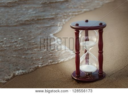 sand timer on beach with tide coming in and vignette lighting