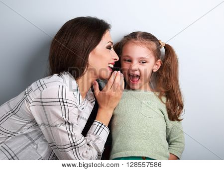 Joying Young Mother Whispering The Secret To Her Funny Grimacing Daughter In Ear In Studio.
