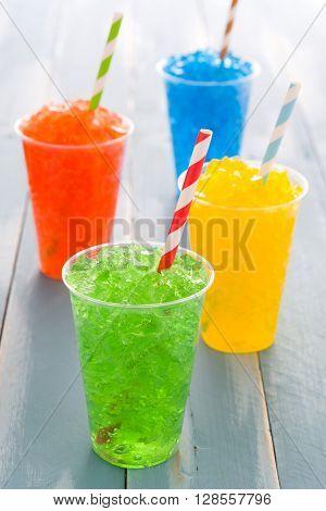 Colorful summer fresh slushies on blue wood