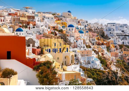 Picturesque view of white houses, windmills and church with blue domes in Oia or Ia, island Santorini, Greece