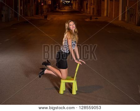 model woman kneeling on chair in the street at night