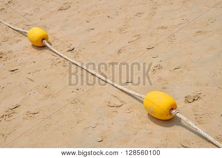Two Yellow Marker Buoys On Sand Beach