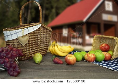 Picnic Table With Two Baskets And Fruits Near Country House