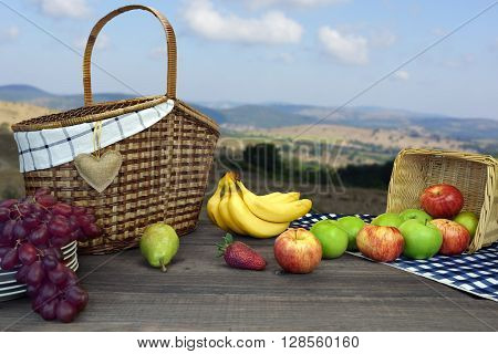 Picnic Table With Two Baskets And Fruits And Mountain Landscape