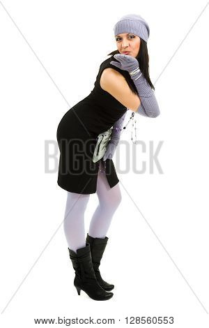 knitwear. young woman wearing a winter cap and gloves, isolated on white background in full length.