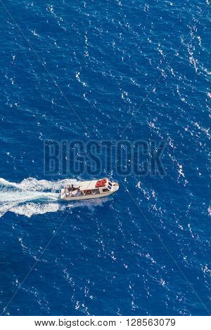Top view on a  boat in azure water