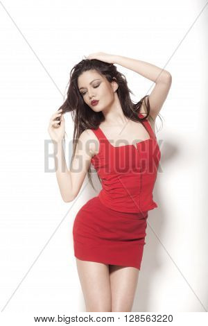 Brunette woman in a red dress isolated on a white background.