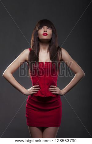 Brunette woman in a red dress on a dark background.