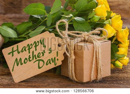 bunch of yellow roses  on wooden background with happy mothers day  paper tag gift box close up