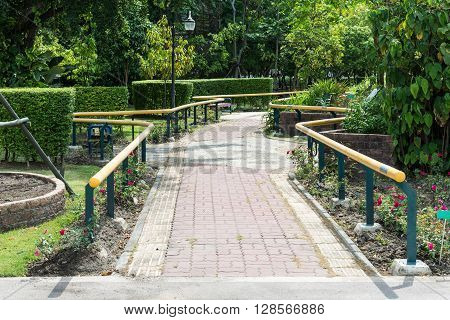 Stone tile pathway with metal handrails in the botanical garden.