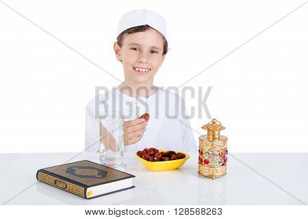 Young Muslim boy holding dates ready for brakfast in Ramadan - sitting on a table with water dates Quran and Ramadan lantern